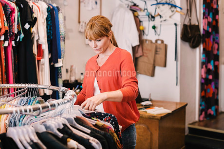 Owner arranging clothes on rack while standing at thrift storeの写真素材 [FYI02137218]