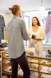 Happy female customer standing with male owner at checkout counter in boutiqueの写真素材 [FYI02137250]