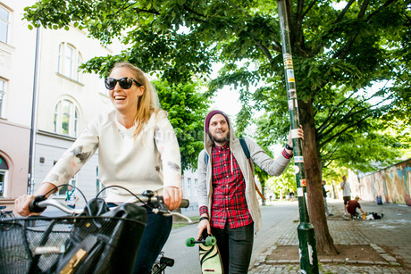 Man holding skateboard and pole while walking by woman on bicycleの写真素材 [FYI02137298]