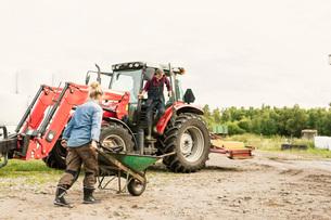 Woman pushing wheelbarrow towards man and tractor at farmの写真素材 [FYI02137511]
