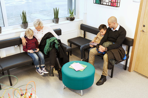 Families using technologies while waiting in orthopedic clinicの写真素材 [FYI02137513]