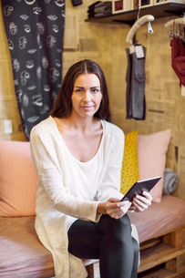 Portrait of female owner using digital tablet at clothing storeの写真素材 [FYI02137520]