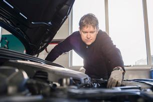 Mechanic repairing car engine in auto repair shopの写真素材 [FYI02137545]
