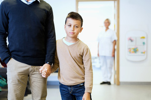 Portrait of boy holding father's hand with nurse in background at orthopedic clinicの写真素材 [FYI02137547]