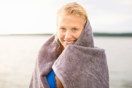 Portrait of smiling woman wrapped in towel against lakeの写真素材 [FYI02137580]