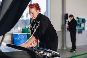 Female mechanic repairing car while colleague standing in background at auto repair shopの写真素材 [FYI02137583]