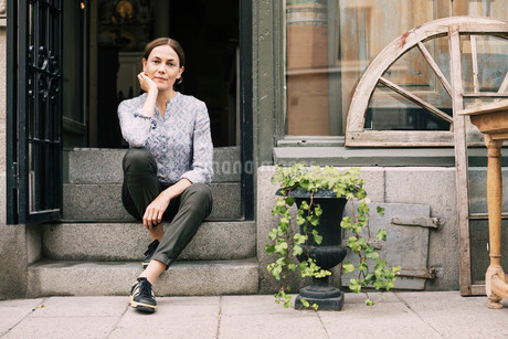 Portrait of female owner with hand on chin sitting on steps at storeの写真素材 [FYI02137601]
