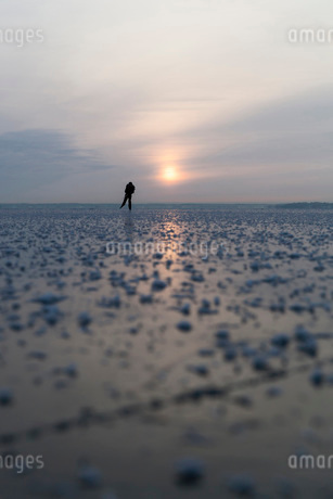 Distant view of woman ice-skating on frozen lake during sunsetの写真素材 [FYI02137617]