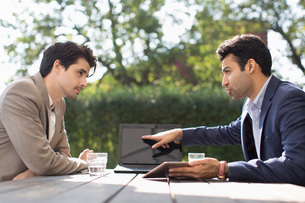 Businessman discussing with male colleague through laptop at outdoor cafeの写真素材 [FYI02137650]