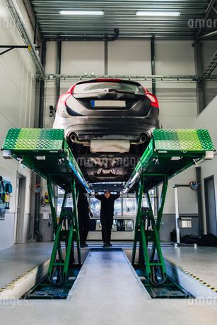 Car on hydraulic lift in auto repair shopの写真素材 [FYI02137687]
