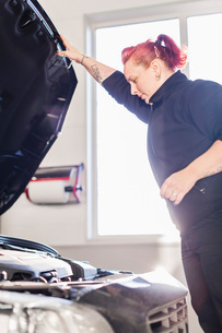 Female mechanic opening car's hood in auto repair shopの写真素材 [FYI02137707]