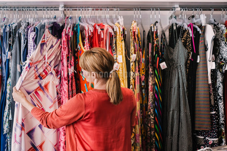 Woman looking at dress hanging on rack while standing at storeの写真素材 [FYI02137736]