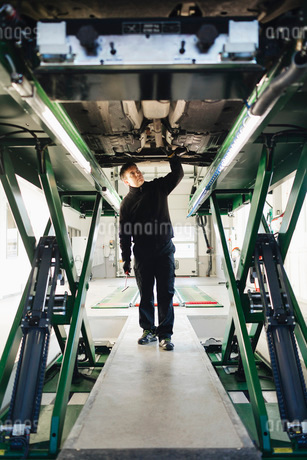 Full length of male mechanic examining car on hydraulic lift in auto repair shopの写真素材 [FYI02137739]
