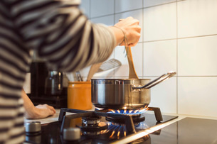 Cropped image of woman holding spatula in sauce pan while cooking food on stoveの写真素材 [FYI02137752]