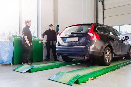 Full length of mechanics looking at car on hydraulic lift at auto repair shopの写真素材 [FYI02137765]