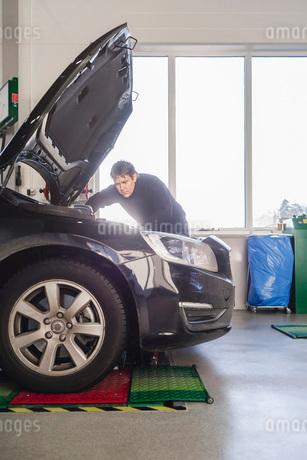 Mechanic repairing car in auto repair shopの写真素材 [FYI02137803]