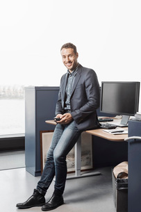 Full length portrait of confident businessman leaning on desk in officeの写真素材 [FYI02137818]