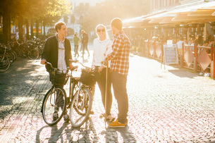 Friends with skateboard and bicycles talking while standing on city streetの写真素材 [FYI02137820]