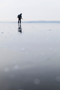 Man ice-skating on frozen lakeの写真素材 [FYI02137821]