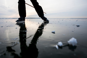 Low section of man ice-skating on frozen lakeの写真素材 [FYI02137845]
