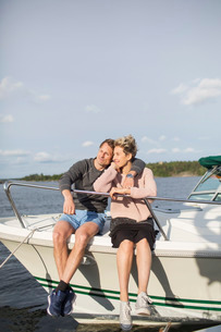 Loving couple sitting on yacht against skyの写真素材 [FYI02137863]
