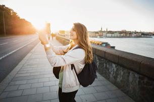 Side view of female tourist photographing through smart phone on bridgeの写真素材 [FYI02137874]