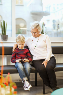 Grandmother and grandson using smart phone while sitting in waiting room of orthopedic clinicの写真素材 [FYI02137904]