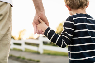 Rear view of father and son holding hands while standing outdoorsの写真素材 [FYI02137969]