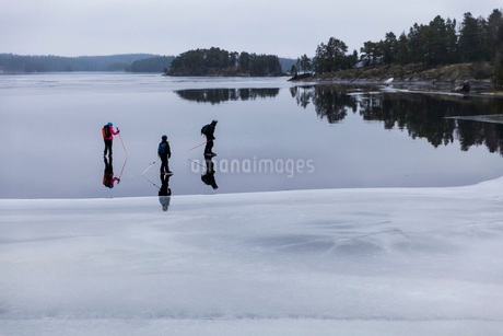 Father and children ice-skating on frozen lakeの写真素材 [FYI02137985]