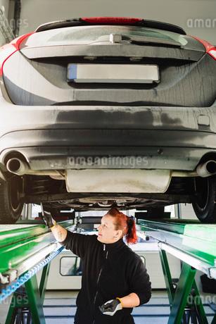 Mechanic examining car with hammer in auto repair shopの写真素材 [FYI02138009]