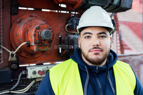 Portrait of confident manual worker standing against machinery in industryの写真素材 [FYI02138018]