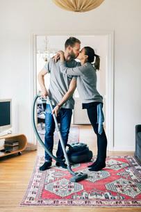 Full length of man kissing woman while vacuuming carpet at homeの写真素材 [FYI02138028]