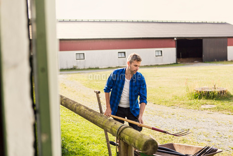 Farmer arranging equipment outside barn at farmの写真素材 [FYI02138030]