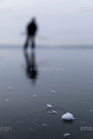 Frozen lake with man ice-skating in backgroundの写真素材 [FYI02138089]