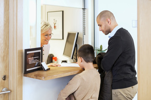 Senior female receptionist giving medical documents to family in orthopedic clinicの写真素材 [FYI02138106]