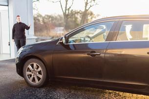 Man driving car while female mechanic guiding him outside auto repair shopの写真素材 [FYI02138134]