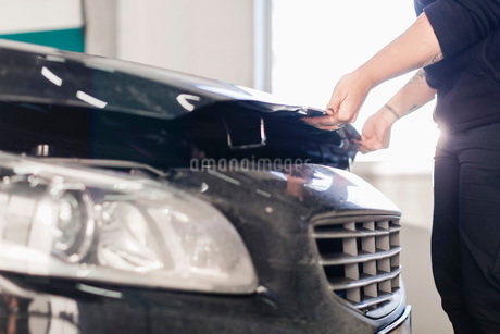 Midsection of mechanic opening car's hood in auto repair shopの写真素材 [FYI02138155]