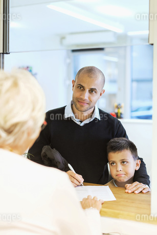 Father and son looking at receptionist while filling forms in orthopedic clinicの写真素材 [FYI02138157]