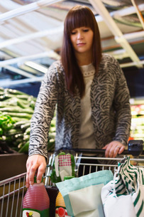 Woman arranging groceries in shopping cart at supermarketの写真素材 [FYI02138164]