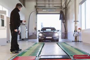 Full length of mechanic guiding car coming towards hydraulic liftの写真素材 [FYI02138185]