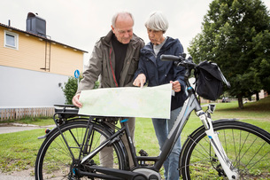 Senior couple searching places on map by bicycle at yardの写真素材 [FYI02138191]