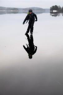 Full length of boy ice-skating on frozen iceの写真素材 [FYI02138194]