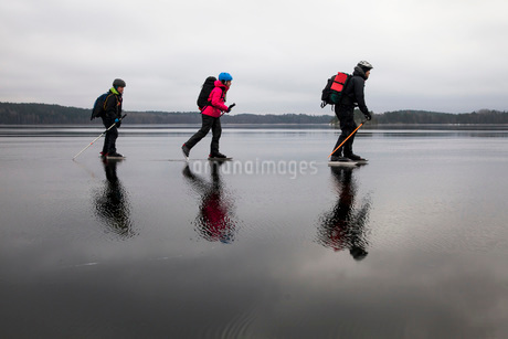 Full length side view of father and children ice-skating on frozen lakeの写真素材 [FYI02138199]