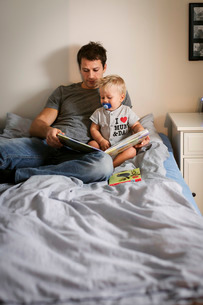 Man reading book with baby boy in bedroomの写真素材 [FYI02138208]