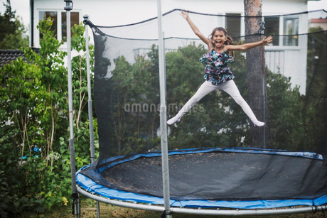 Portrait of excited girl jumping on trampoline at yardの写真素材 [FYI02138212]