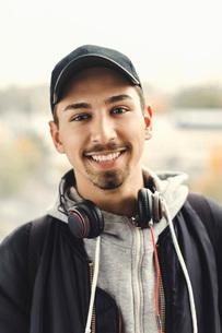 Portrait of happy university student with headphones around neck outdoorsの写真素材 [FYI02138221]