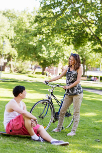 Couple with skateboard and bicycle in parkの写真素材 [FYI02138285]