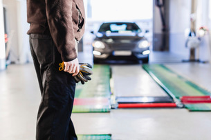 Midsection of mechanic standing in front of car coming towards hydraulic liftの写真素材 [FYI02138294]