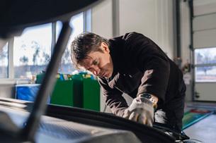 Male mechanic repairing car in auto repair shopの写真素材 [FYI02138336]