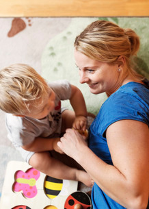 High angle view of mother playing with baby at homeの写真素材 [FYI02138339]